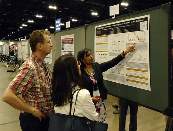 Prahatha presenting her poster to colleagues, including Dr. Stephan Neuhauss on the left.