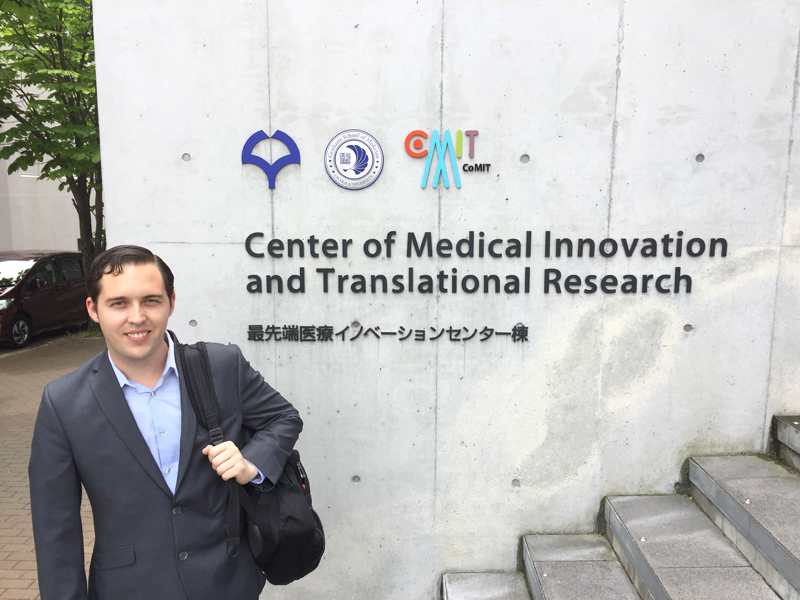 Logan in front of a new Center for Medical Innovation and Translational Research.